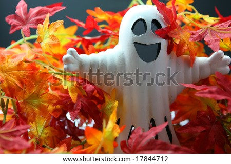 white halloween ghost in between of colorful autumn leaves