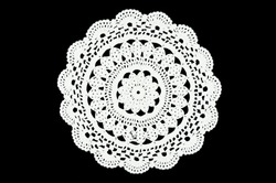 White hand made crocheted coaster lace doily on black background.