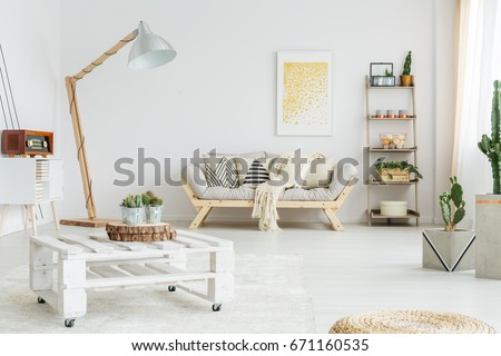 White hand-made pallet table with plants in living room