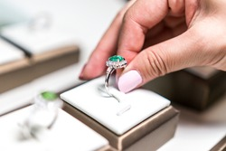 White hand picking up wedding emerald ring in a box