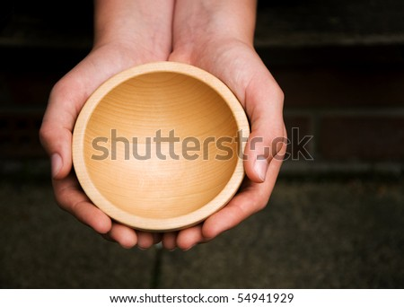 White hands holding a wooden begging bowl