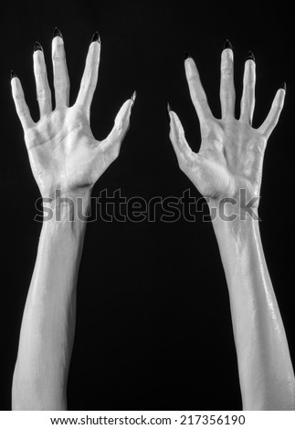 white hands of death with black nails, white death, the devil\'s hands, the hands of a demon, white skin, halloween theme, black background, isolated