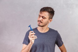 white handsome man holding razor blade.
