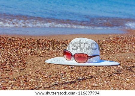 White hat and sunglasses left on the sand at the beach