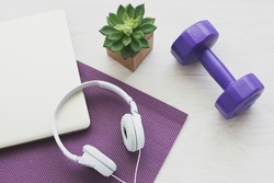 White headphones and dumbell on yoga mat. Concept of Podcast,healthy lifestyle,workout at home,online workout,home excercise.