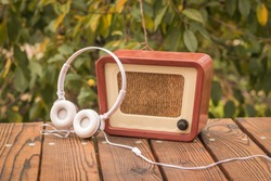 White headphones near an old-fashioned radio on an autumn background. An old technique for listening to radio broadcasts.
