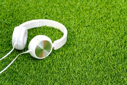White headphones on a green grass, relax concept