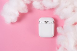 White headphones with box case on pink background. Modern technology pods with air connection. Wireless earphones device. New way to leasten music. Concept of free choice.