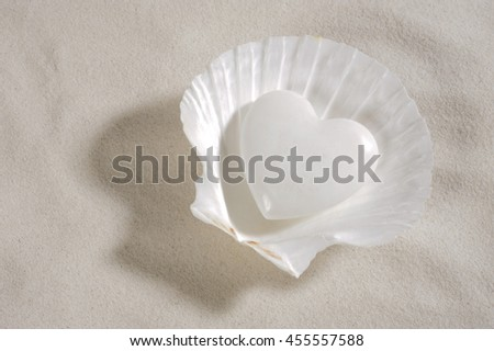 Stock Photo white heart laying in mussel and in white sand as symbol for love