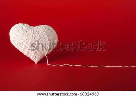 White heart made of wool on a red background. Valentine's Day.