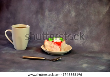 White high ceramic mug with black coffee, next to a plate with a piece of biscuit cake and a teaspoon on a gray background. Close-up.