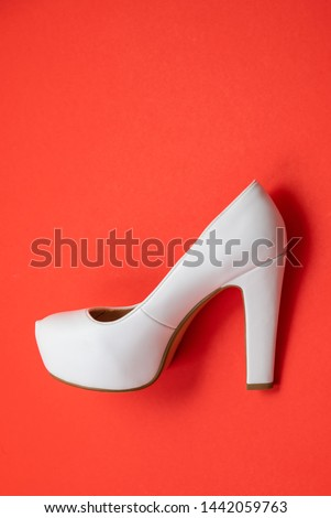 White high heeled shoes on red background - top view concept - blank empty room space for text or copy. Suitable for holidays like Valentine's or Christmas. Classic dress up fashion. Profile of heel #1442059763