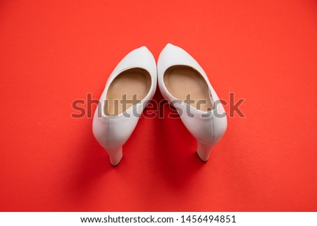 White high heeled shoes on red background - top view concept - blank empty room space for text or copy. Suitable for holidays like Valentine's or Christmas. Classic dress up fashion. Heels pigeon toed #1456494851