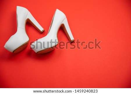 White high heeled shoes on red background - top view concept - blank empty room space for text or copy. Suitable for holidays like Valentine's or Christmas. Classic fashion. Heels walking left #1459240823