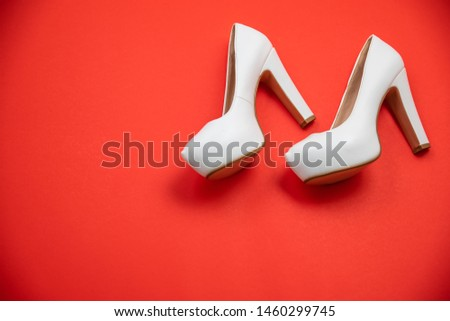 White high heeled shoes on red background - top view concept - blank empty room space for text or copy. Suitable for holidays like Valentine's or Christmas. Classic fashion. Heels walking left #1460299745