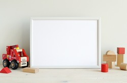 White horizontal frame mockup for printable art, photo, nursery or kids room empty frame mock up, red toys.