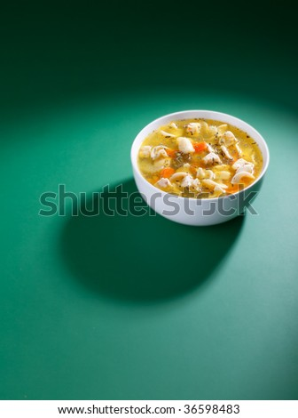 White hot bowl of soup on green background