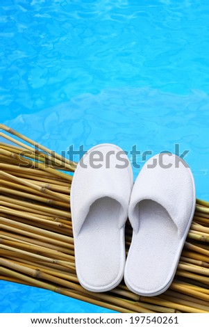 White hotel / home/ spa / wellness slippers on bamboo desk with swimming pool background with space for text - summer time