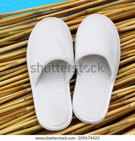 White hotel / home/ spa / wellness slippers on bamboo wood with sea - swimming pool background with space for text