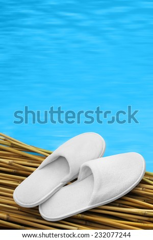 White hotel / home/ spa / wellness slippers on bamboo wood with swimming pool - water - sea background with space for text - summer time
