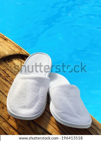 White hotel / home/ spa / wellness slippers on wood with swimming pool background with space for text - summer time