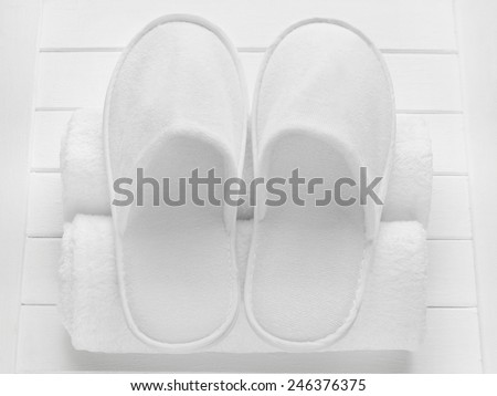 White hotel / home/ spa / wellness slippers with rolled towels on light wooden desk - summer sauna time