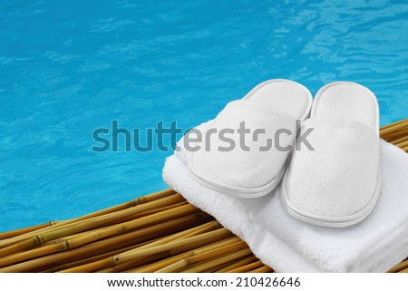 White hotel / home/ spa / wellness slippers with towel on bamboo wood with swimming pool - water - sea background with space for text - summer time