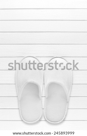White hotel / home/ spa / wellness slippers with towel on light wood desk with space for text - summer sauna time