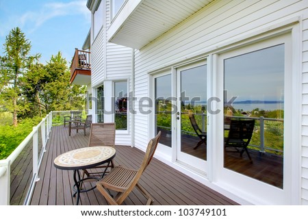 White house balcony deck with furniture and large doors.