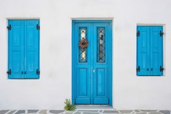 White house facade with traditional blue door on Paros island, Cyclades, Greece