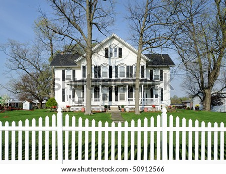 White house with black shutters and white picket fence