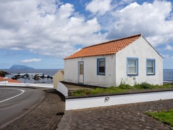 White house with ceramic tiles with the atlantic ocean in the background. In the distance, the island of Corvo. Santa Cruz das Flores, Flores Island.