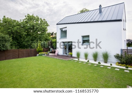 White house with windows and green garden with trees outside