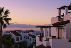 White houses in the sunset light on a pink sky background. Tenerife Spain.