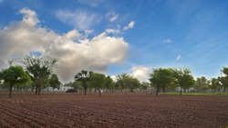 White hovering clouds sky with desolate field. Barren empty field with blue sky nature in countryside India.
