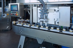 White ice cream in cake cone plant production conveyor line with cream filler equipment, control computer device. Food industry  manufacturing line with digital control. Traditional Russian ice cream