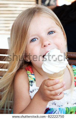 White ice cream in hand of beautiful little blonde girl