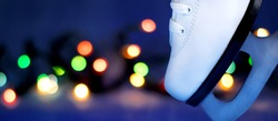 White ice skate standing on the blade against the blurred Christmas lights. Copy space. Ice skating in the night rink. Winter holidays pastime activity