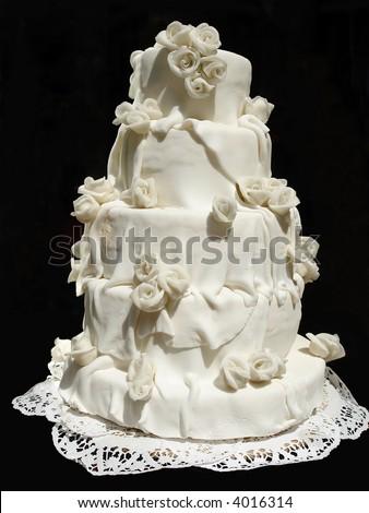 White iced wedding cake isolated on black background