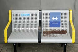 White icons and letters on blue sign on public bench says: