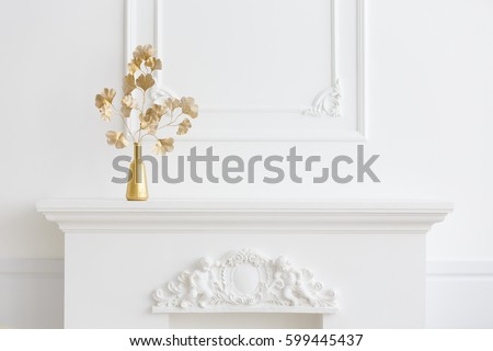 white interior. white fireplace in a light interior and a gold vase. Classical interior