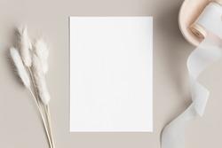 White invitation card mockup with a lagurus on a beige table. 5x7 ratio, similar to A6, A5.