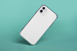 White iPhone 11 in clear silicone case falls down isolated on green background back view. iPhone 12 case mockup
