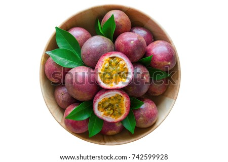 White isolated background of ripe fresh passion fruit in wood bowl in top view flat lay with copy space. Tropical fruits so delicious with sweet and sour taste.