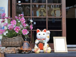 White Japanese cat of luck or fortune (Maneki-neko).  Beckoning Cat, outside a store. Common Japanese figurine (lucky charm, talisman) which is often believed to bring good luck to the owner