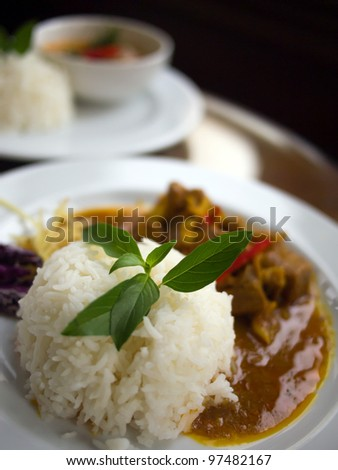 White jasmine rice with green herb on top and pork in red curry. Behind is rice with chicken in green curry. Black background