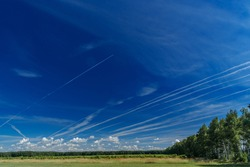 White jet passenger plane flying at high altitude in the blue sky. White traces of condensation of water vapor in the form of lines from flying aircraft over the field and trees.