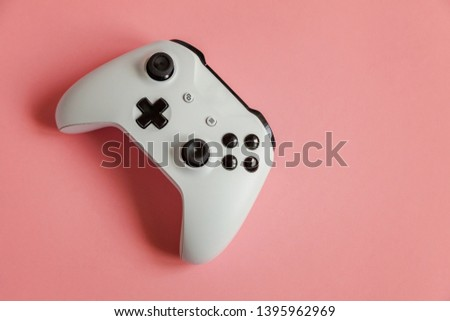 White joystick gamepad, game console on pastel pink colourful trendy modern pin-up background. Computer gaming competition videogame control confrontation concept. Cyberspace symbol