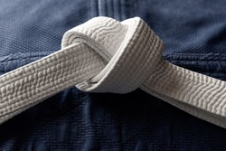 White judo, aikido or karate belt on blue budo gi. Concept is applicable to sports, business or education