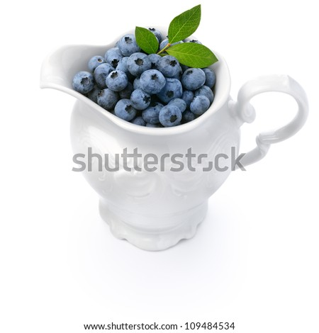 White jug full of blueberries isolated over white